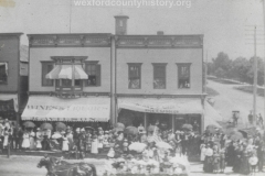 Cadillac-Parade-Early-1900s-parade-On-The-Corner-Of-Cass-And-South-Mitchell-Wilsons-Saloon-and-the-Rice-And-Cassler-Business-are-in-the-background