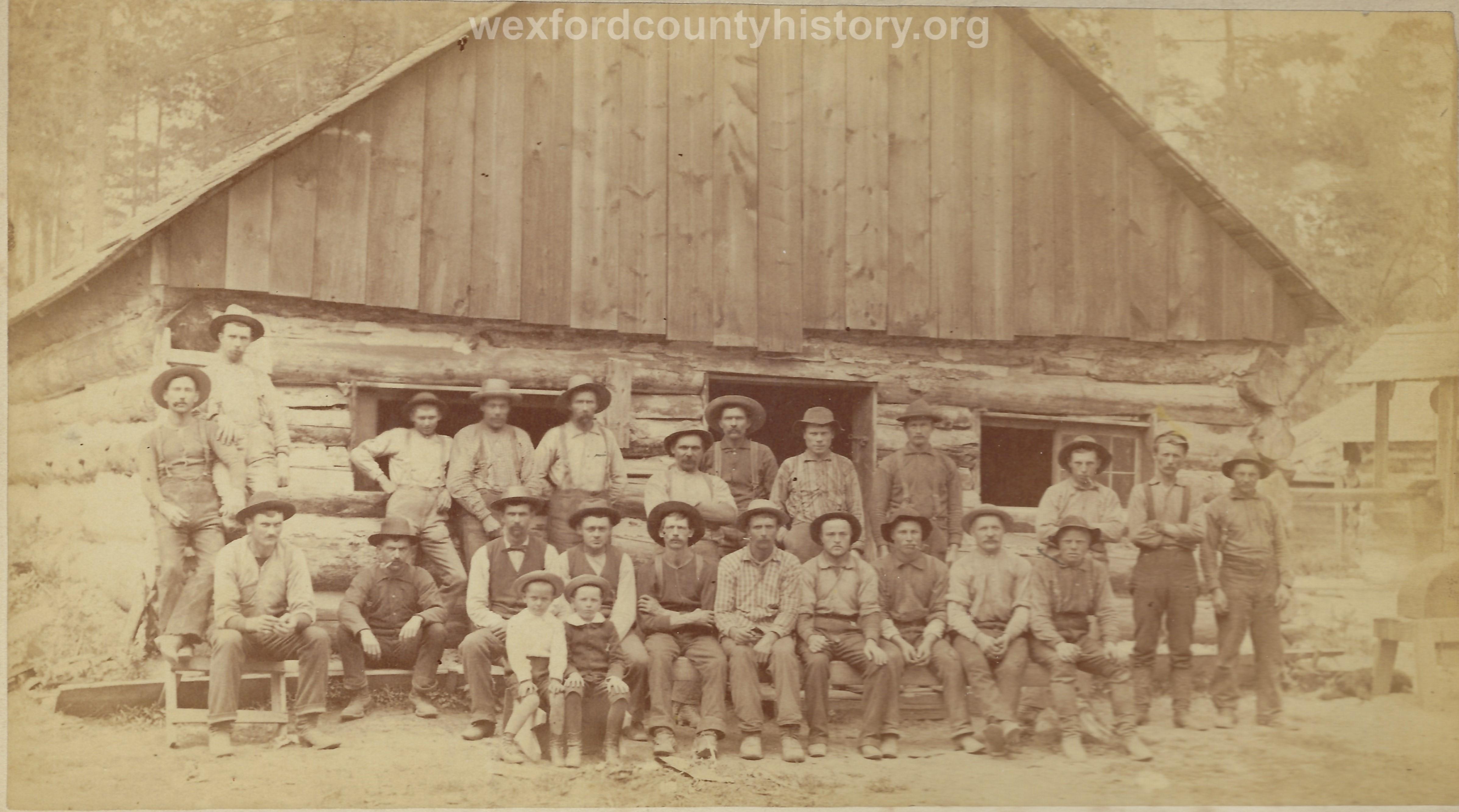 Cadillac-Lumber-Lumberjacks-Posing-In-Front-Of-Camp-Building-1
