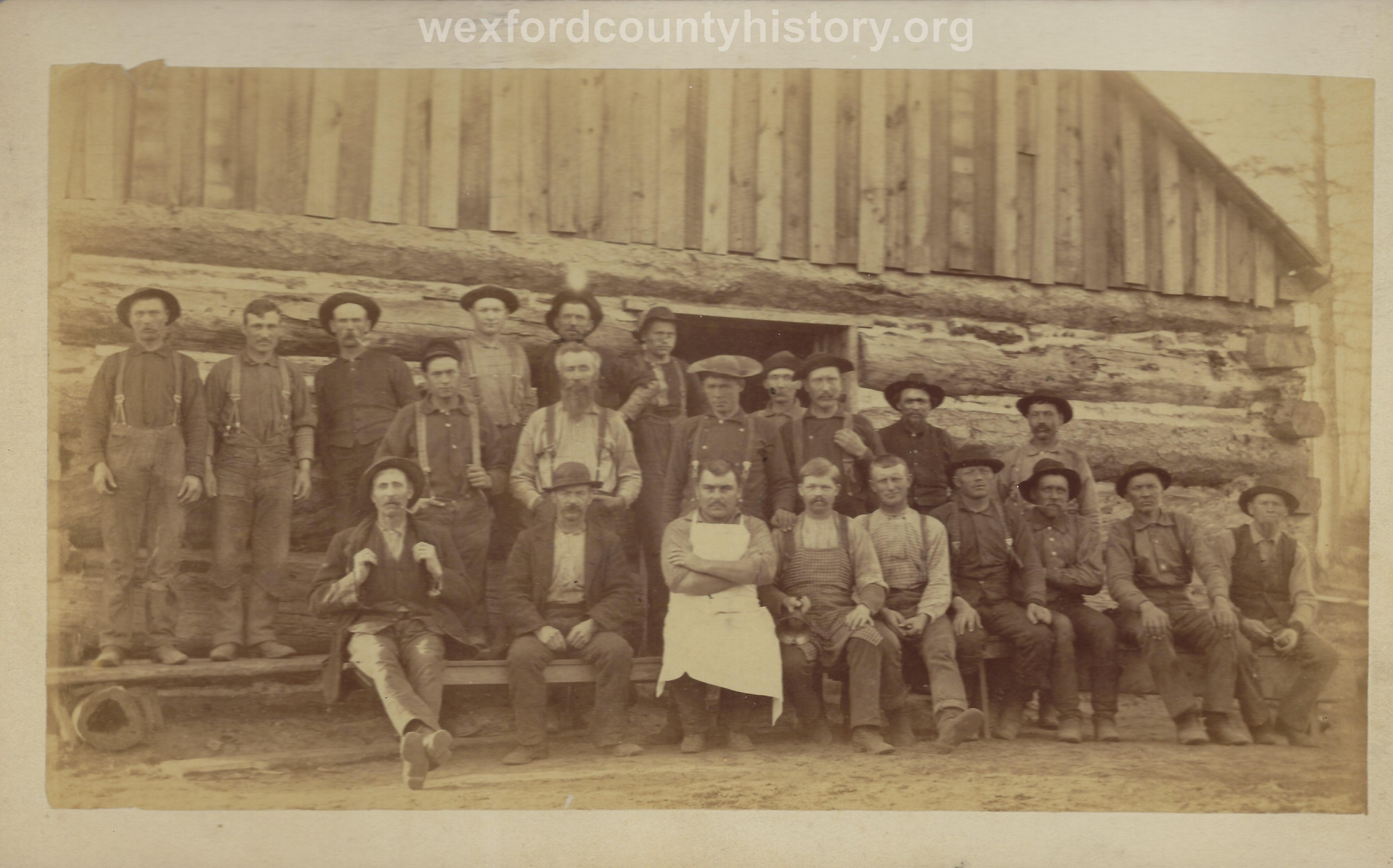 Cadillac-Lumber-Lumberjacks-Posing-In-Front-Of-Camp-Building