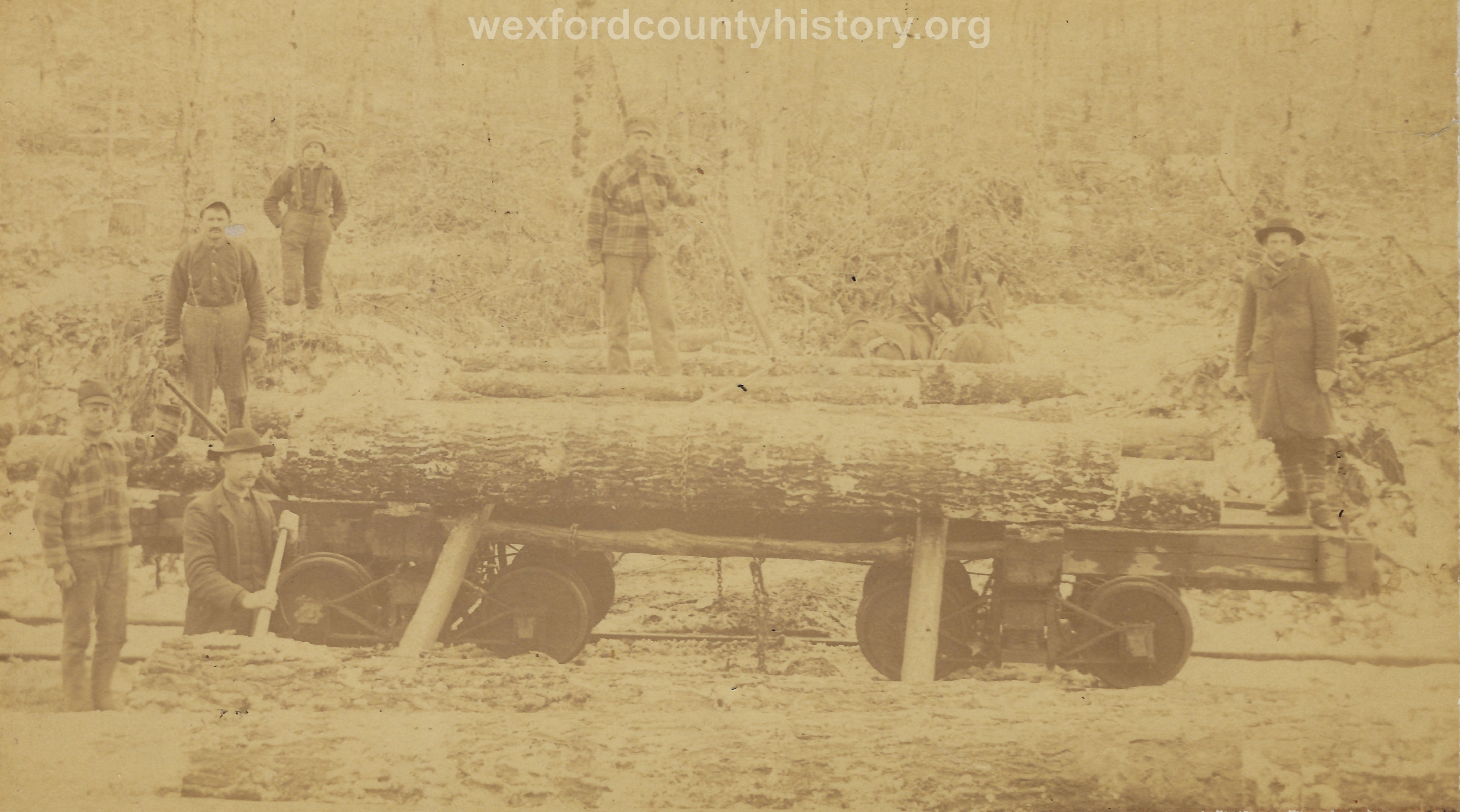 Cadillac-Lumber-Lumberjacks-loading-logs-into-railroad-car-with-a-light-snow-on-the-logs