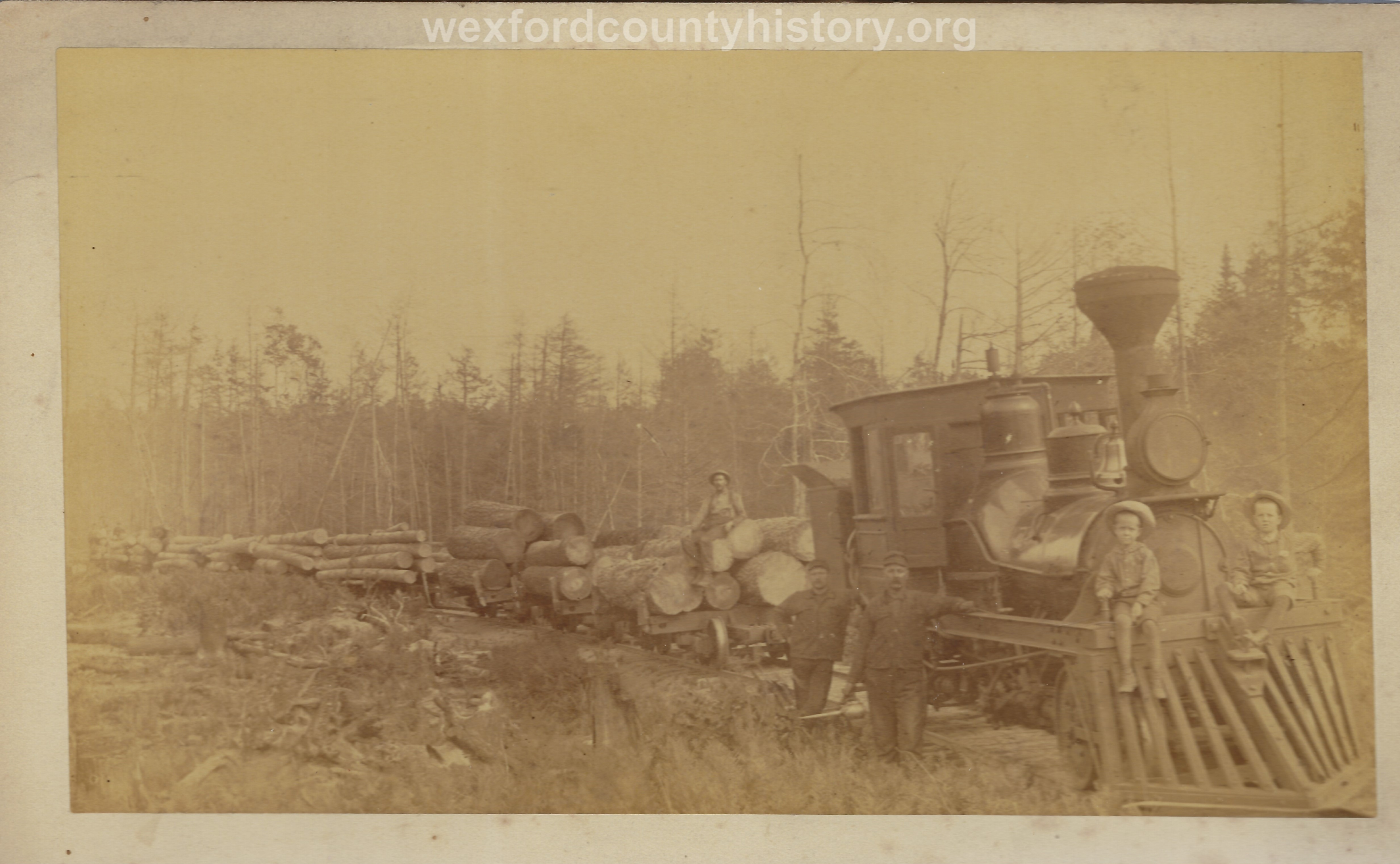 Cadillac-Lumber-Engine-Pulling-Nine-Cars-Of-Logs-With-Children-Posed-On-Cow-Catcher
