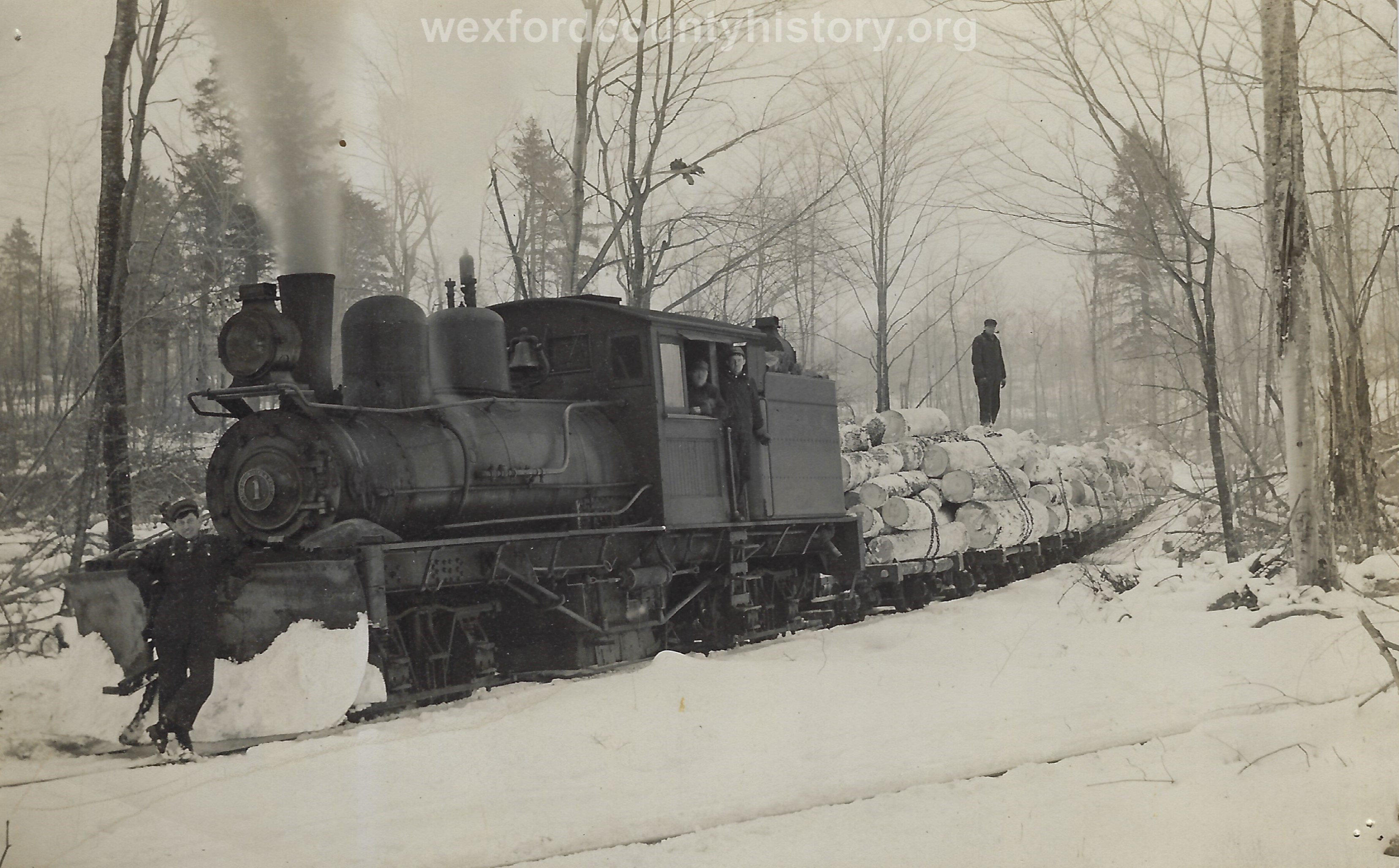 Cadillac-Lumber-Locomotive-With-Plow-Attachement-Pulls-Logs-From-The-Wilderness